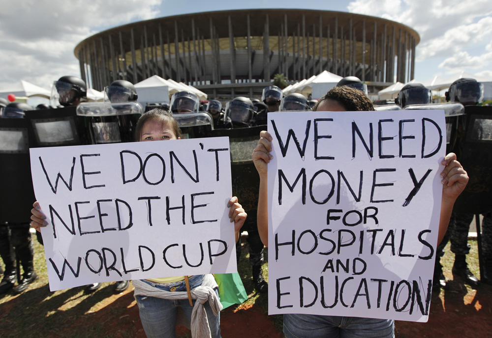 Activists demonstrate in front of riot police outside the Mane Garrincha National Stadium in Brasilia